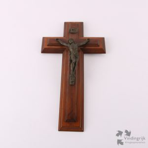 Crucifix met bronskleurige Christus op een houten kruis in Art Deco stijl. Aan de achterzijde zit een metalen ring om het kruis aan de wand te hangen.