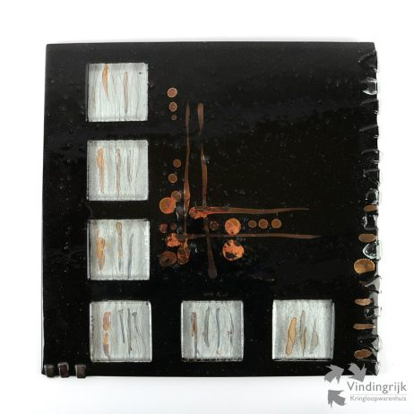 Anastasia (Thessaloniki 1956) is een Griekse kunstenares, gespecialiseerd in glasbewerking. Hier een wanddecoratie van haar eigen merk Glass Design, volledig met de hand vervaardigd. Het werk heeft 6 transparante vierkanten, bespannen met metalen draden, die op het vlak liggen. Voorts is ook metaal ingewerkt in het glas. Aan de zijkant rechts ontbreekt 1 transparante glazen druppel. De achterzijde heeft een ingesmolten metalen plaat met inkeping om het object aan op te hangen. Gemaakt in Griekenland.